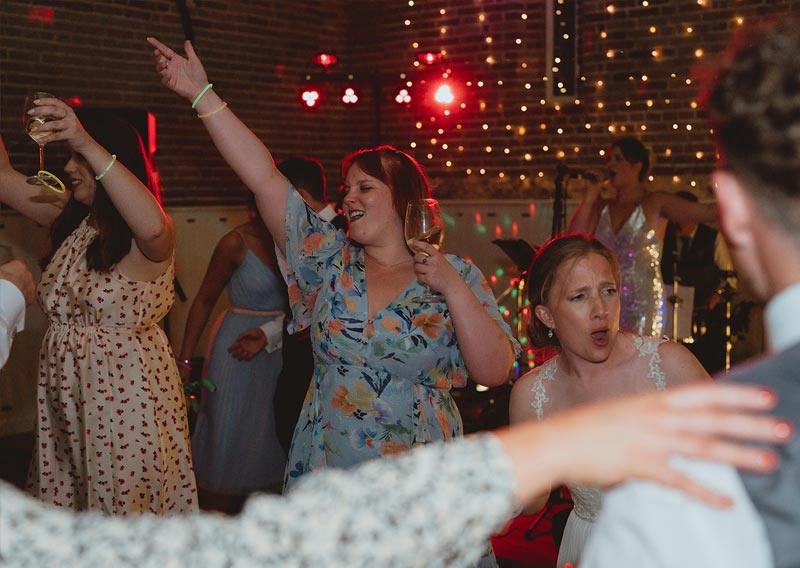 Woman with her hand up dancing at wedding reception