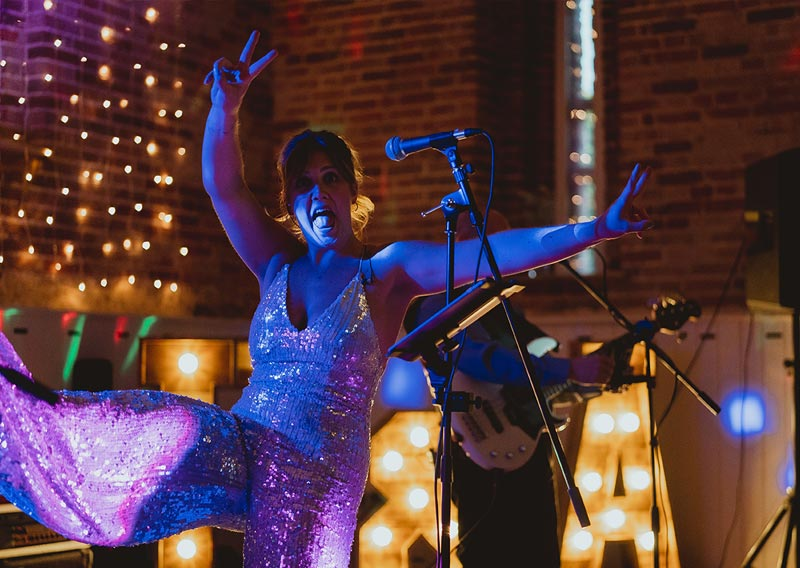 Charlie from Electric Outfit dancing on stage at wedding reception