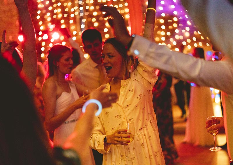 Woman dancing at wedding, hands in the air